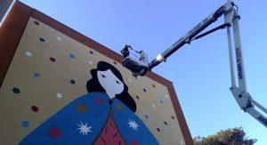 """<p>""""'A Mamm' 'e Tutt' 'e Mamm'"""": si chiama così l'ultimo murale che sta ridipingendo il volto del Parco dei Murales di Napoli Est a Ponticelli. L'opera, realizzata dall'artista sarda La Fille Bertha, vuole celebrare il valore della maternità e ricopre, anche questo, l'intera facciata di un palazzo. Il progetto del Parco nasce con l'intento di [&hellip;]</p>"""