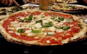 """<p>In un famoso film americano, una certa Julia, addentando uno spicchio di Margherita ancora fumante, dichiarava di """"avere una storia d'amore con la pizza"""". In effetti, a tutte le latitudini, quello con la pizza è amore al primo morso. È buona, è semplice, è economica. Ma è davvero napoletana? Sull&#8217;""""invenzione"""" della pizza abbondano gli aneddoti [&hellip;]</p>"""